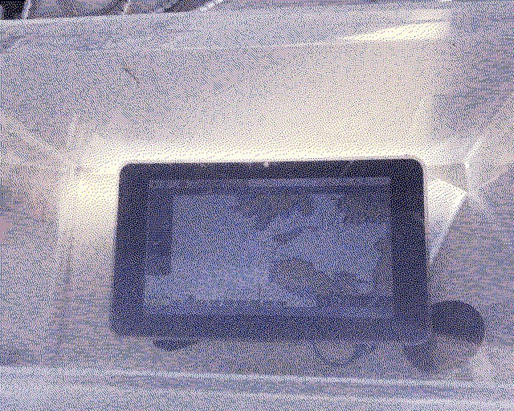 En kartplotter nede i en plastikkboks. Under den ligger en en powerbank og GPS-mottaken. Alt ligger i cockpiten i en båt.